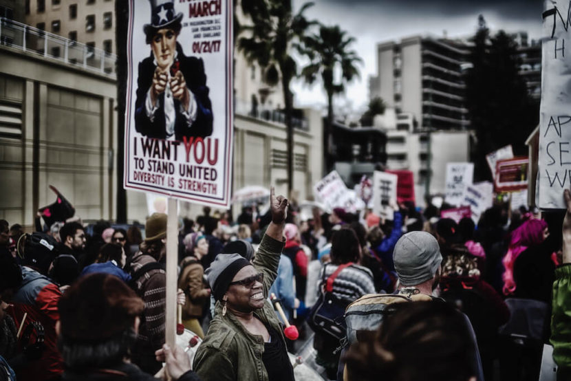 "Image Description: An image from a protest featuring a sign with Uncle Sam which reads ""I Want You To Stand United: Diversity is Strength"""