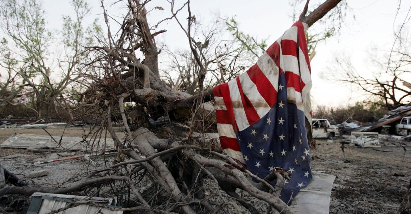 Image Description: A picture of fallen trees draped with the American flag